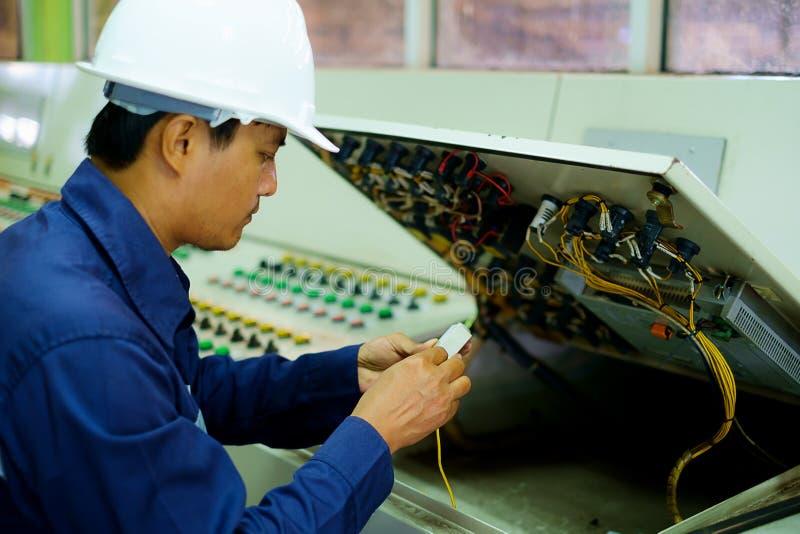 Inżynier sprawdza instalację elektryczną i naprawia obraz stock