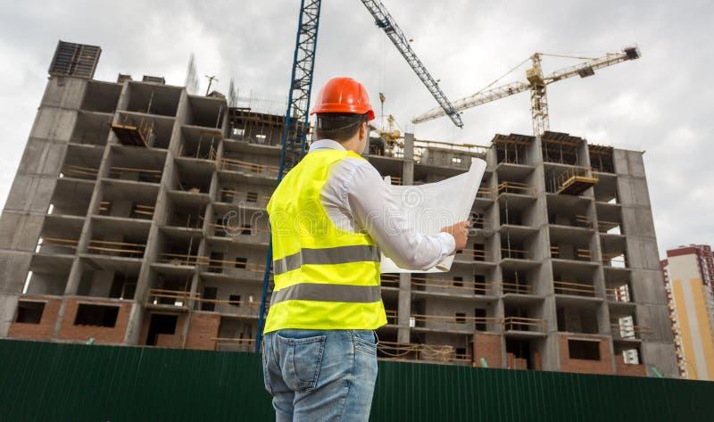 Inżynier sprawdza plany i projekty na placu budowy zdjęcia royalty free