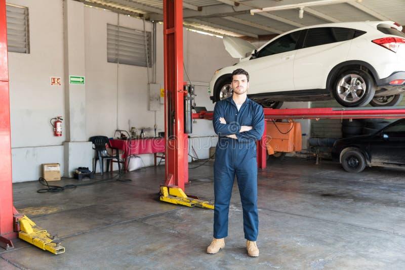 Inżynier Stoi ręki Krzyżować Przeciw Samochodowemu dźwignięciu W Coveralls obrazy stock