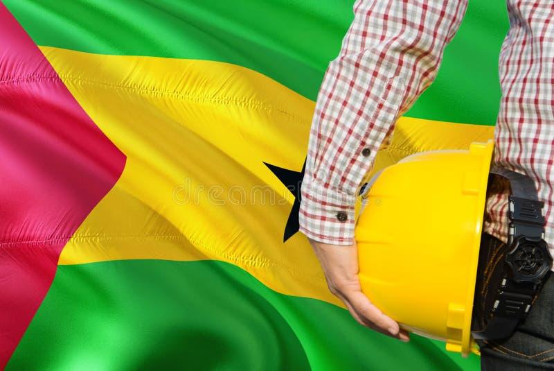 Inżynier trzyma żółtego zbawczego hełm z falowania Sao Principe I woluminu chorągwianym tłem Budowy i budynku poj?cie zdjęcia stock