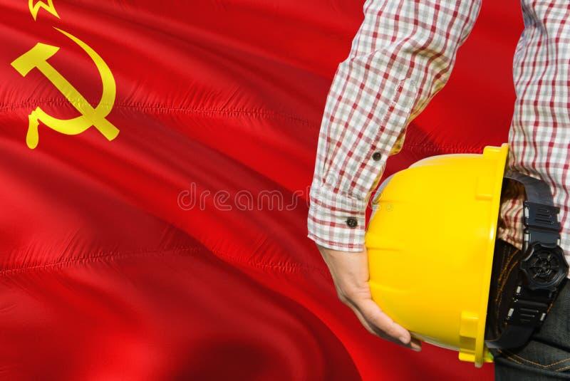 Inżynier trzyma żółtego zbawczego hełm z falowanie sowieci - zrzeszeniowej flagi tło Budowy i budynku poj?cie zdjęcia stock