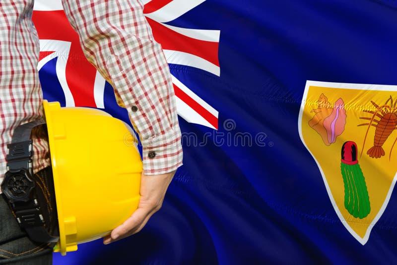 Inżynier trzyma żółtego zbawczego hełm z falowanie turczynkami I Caicos wysp chorągwianym tłem Budowy i budynku poj?cie zdjęcia stock