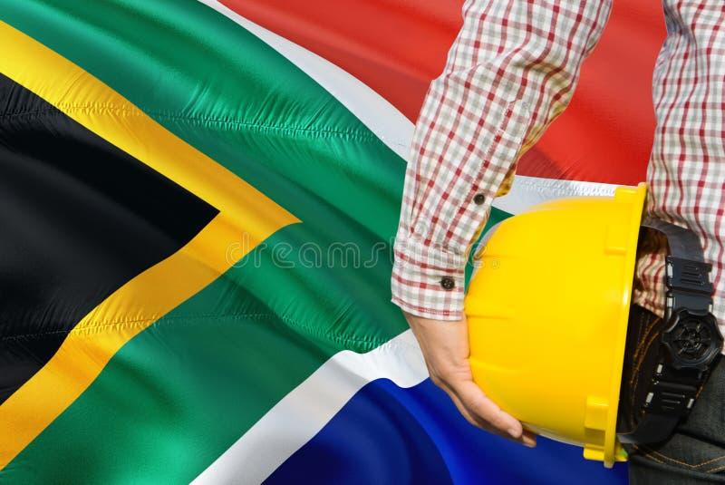 Inżynier trzyma żółtego zbawczego hełm z machać Południowa Afryka chorągwianego tło Budowy i budynku poj?cie fotografia royalty free