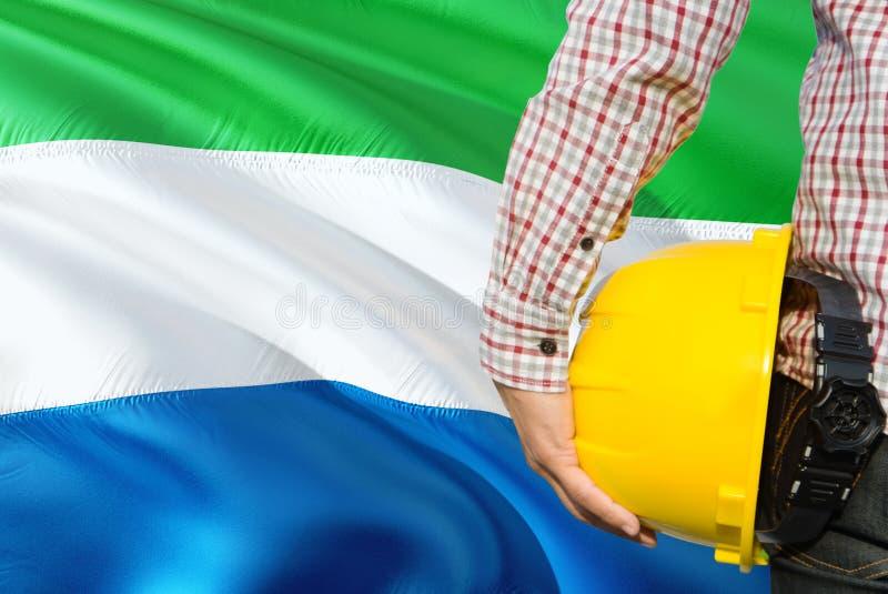 Inżynier trzyma żółtego zbawczego hełm z machać Sierra Leone chorągwianego tło Budowy i budynku poj?cie obrazy royalty free