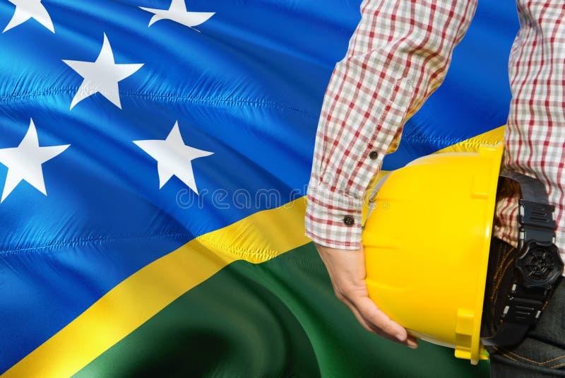 Inżynier trzyma żółtego zbawczego hełm z machać Solomon wysp chorągwianego tło Budowy i budynku poj?cie zdjęcia stock