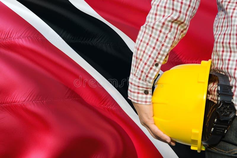 Inżynier trzyma żółtego zbawczego hełm z machać Trinidad I Tobago chorągwianego tło Budowy i budynku poj?cie fotografia stock