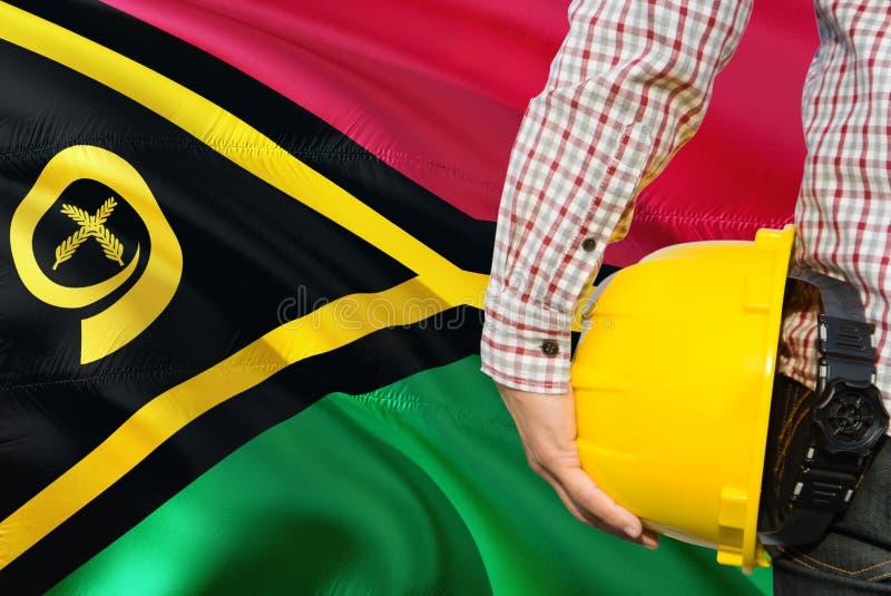 Inżynier trzyma żółtego zbawczego hełm z machać Vanuatu chorągwianego tło Budowy i budynku poj?cie obraz stock