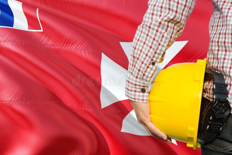 Inżynier trzyma żółtego zbawczego hełm z machać Wallis I Futuna chorągwianego tło Budowy i budynku poj?cie zdjęcia stock