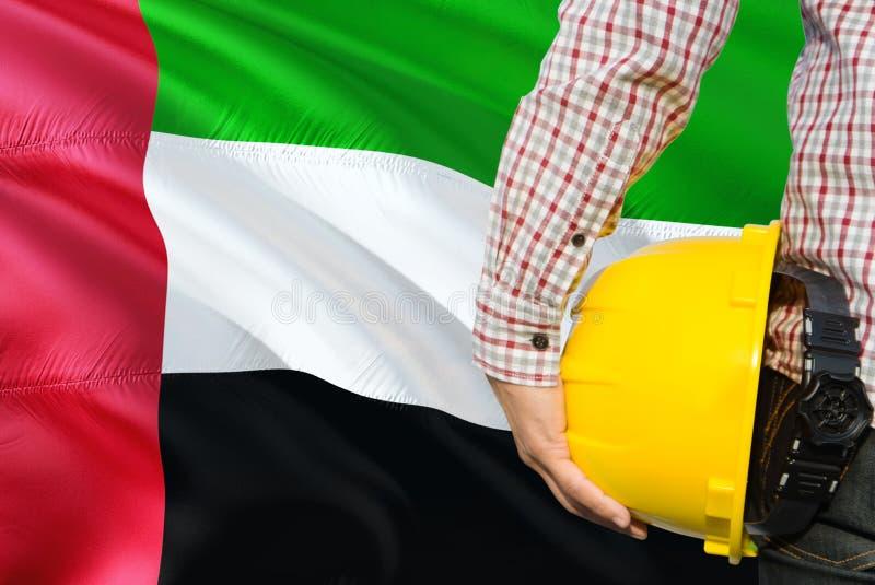 Inżynier trzyma żółtego zbawczego hełm z machać Zjednoczone Emiraty Arabskie chorągwianego tło Budowy i budynku poj?cie zdjęcie stock