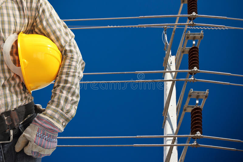 Inżynier z wysokim woltaż elektryczności słupem w niebieskim niebie zdjęcia royalty free