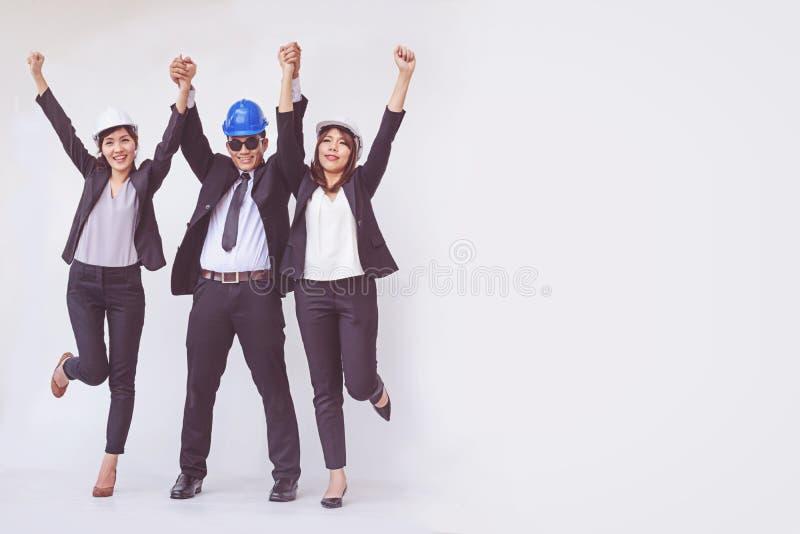 Inżyniera i architekta pozycja z otwartymi rękami wśród szczęśliwego zdjęcia stock