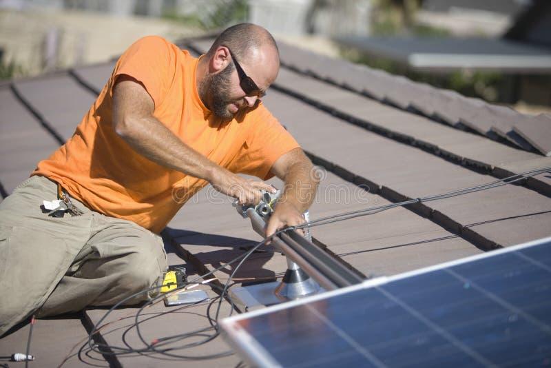 Inżyniera naprawiania panel słoneczny Na dachu fotografia stock