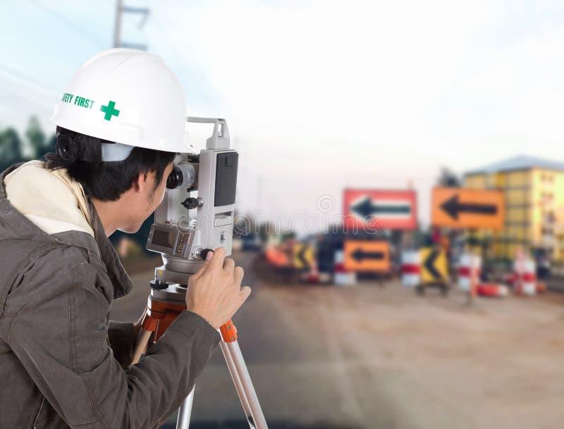 Inżyniera use theodolite z budowy drogą w lub tacheometer fotografia stock