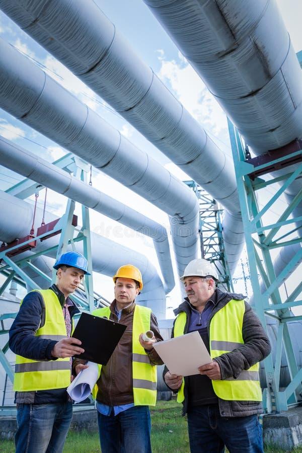 Inżyniery dyskutuje utrzymanie zakład petrochemiczny fotografia royalty free