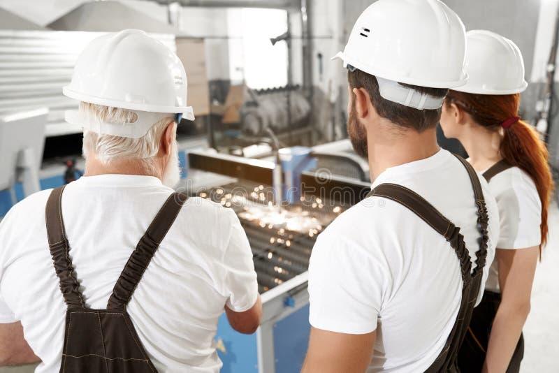 Inżyniery obserwuje osocze laserowego tnącego metal obraz stock