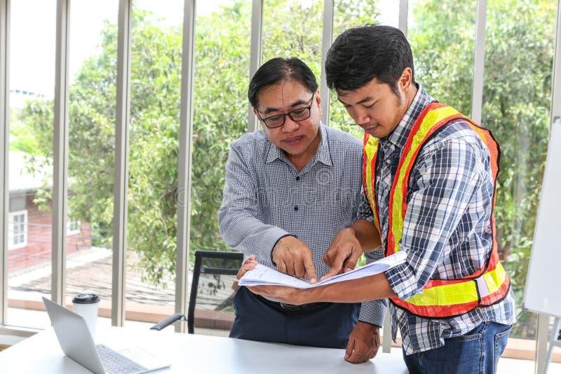 Inżyniery pracuje pokój konferencyjnego przy biurem Trzy pracownika opowiadają budowa plan Elektryka cieśla lub Techniczny zdjęcie stock