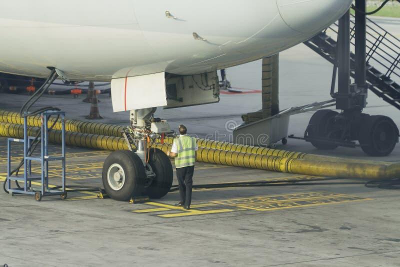Inżyniery sprawdzają frontowych koła samolot fotografia stock