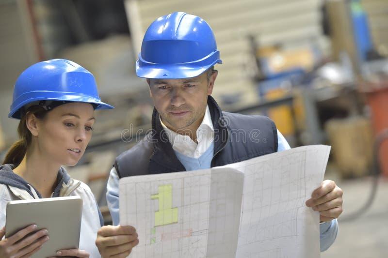 Inżyniery w przemysłowy fabryczny dyskutować obrazy stock