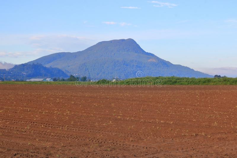 Inactive Volcano and Farm Land. An old inactive volcano overlooks prime agricultural farm land that is ready for seeding royalty free stock photos