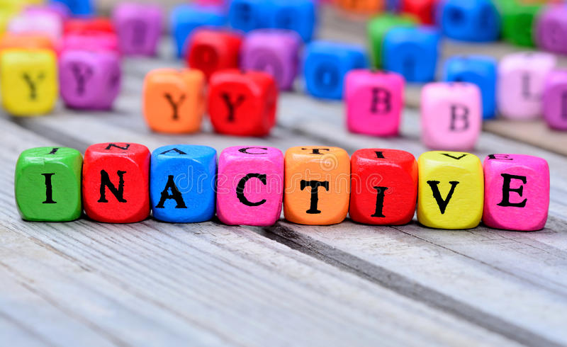 Inactive word on table. Inactive word on wooden table stock photos