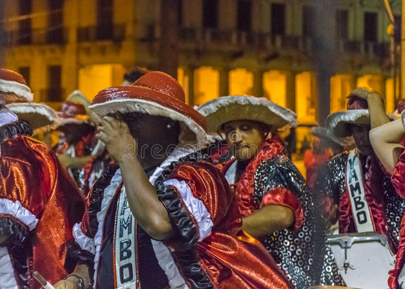 Inagural Parade of Carnival in Montevideo Uruguay. MONTEVIDEO, URUGUAY, JANUARY - 2016 - Costumed men drummers playing traditional music called candombe at the royalty free stock photos
