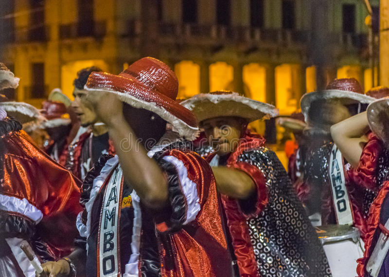 Inagural Parade of Carnival in Montevideo Uruguay. MONTEVIDEO, URUGUAY, JANUARY - 2016 - Costumed men drummers playing traditional music called candombe at the stock photos