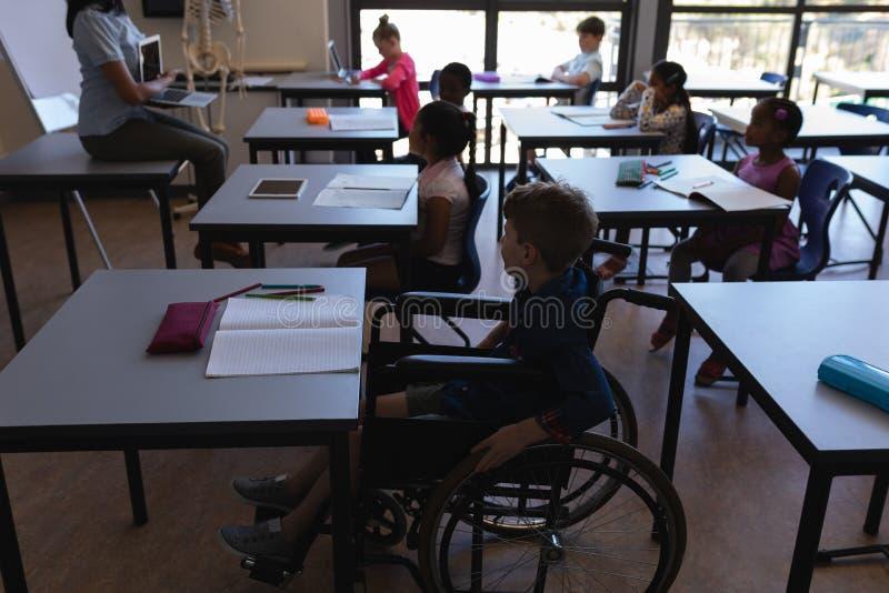 Inaktivera skolpojken med klasskompisar som studerar och sitter på skrivbordet i klassrum arkivfoto
