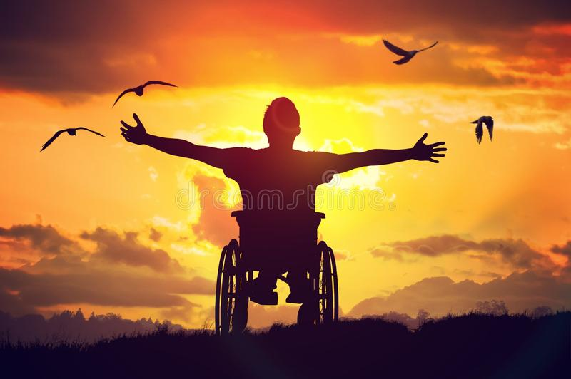 Inaktiverade den handikappade mannen har ett hopp Han sitter på rullstolen och sträcker händer på solnedgången royaltyfri foto