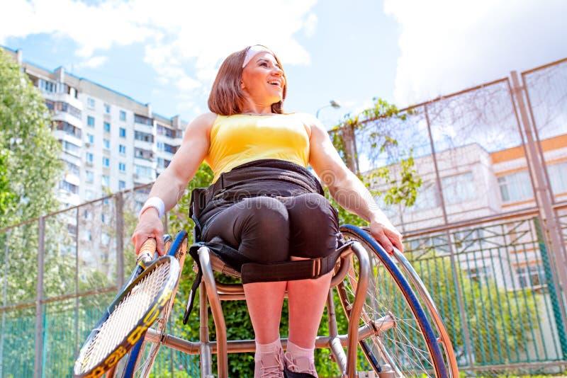 Inaktiverade den unga kvinnan på rullstolen som spelar tennis på tennisbanan royaltyfri fotografi