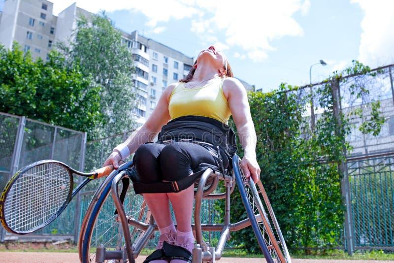 Inaktiverade den unga kvinnan på rullstolen som spelar tennis på tennisbanan royaltyfria bilder