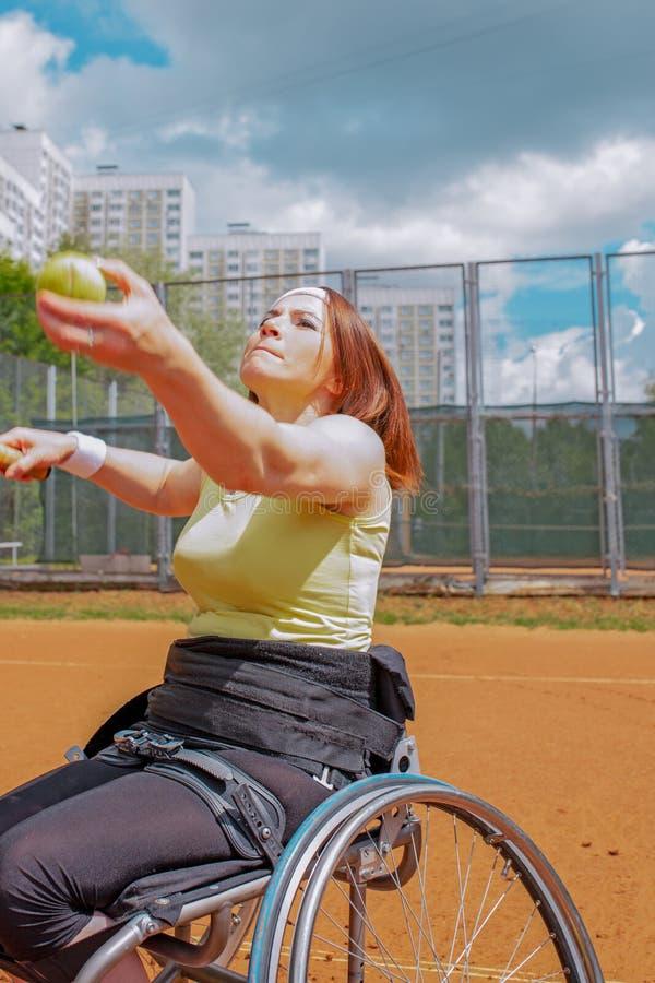Inaktiverade den unga kvinnan på rullstolen som spelar tennis på tennisbanan arkivbilder