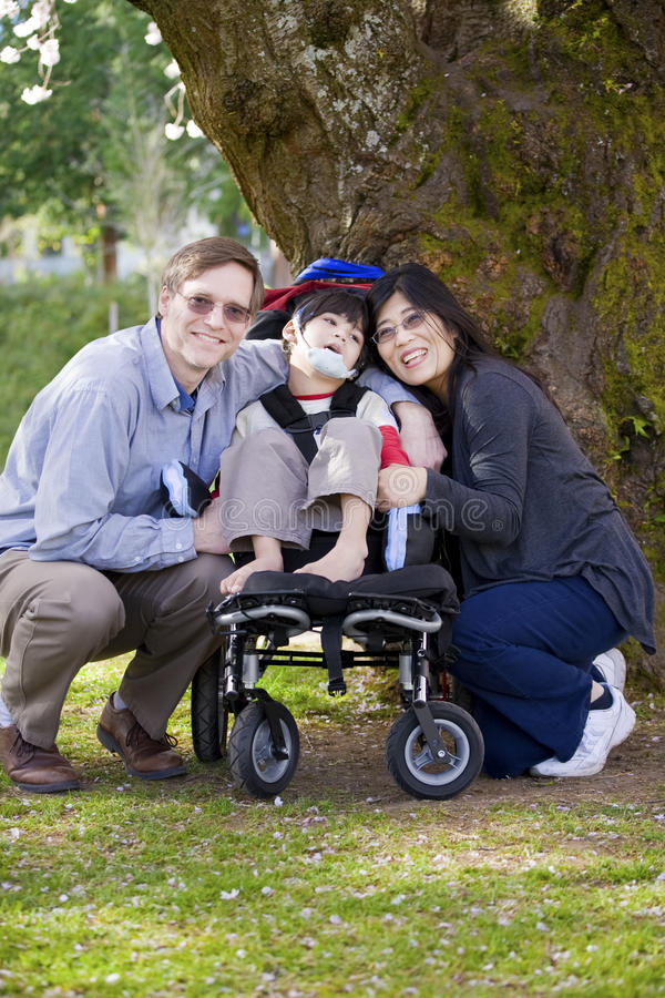 Inaktiverat barn som omges av föräldrar arkivbilder