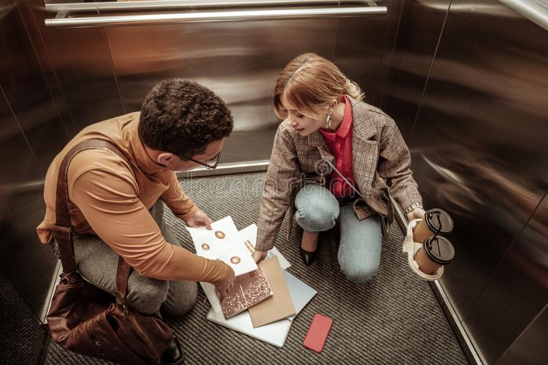 Inattentive woman dropping documents on the floor in elevator. Inattentive woman. Inattentive stylish blonde-haired women dropping documents on the floor in royalty free stock photography