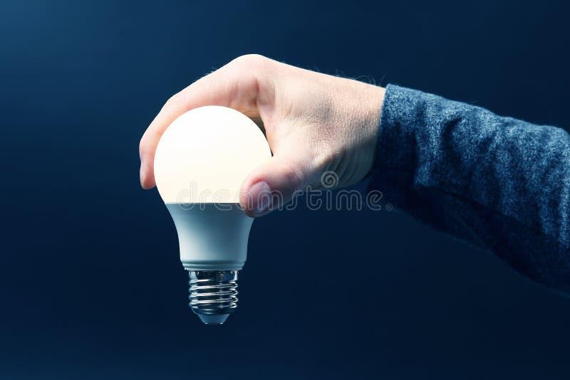 Inbegrepen geleide lamp in menselijke hand op donkerblauwe achtergrond royalty-vrije stock afbeelding