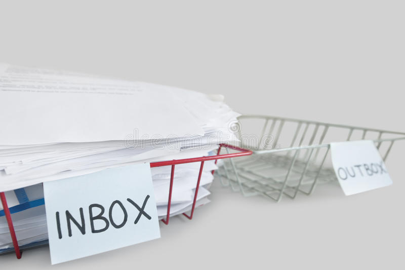 Inbox και outbox δίσκοι σε ένα γραφείο πέρα από το άσπρο υπόβαθρο στοκ φωτογραφίες