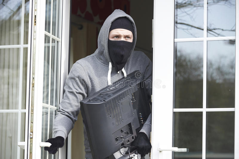 Inbreker Breaking Into House en Stealing Televisie stock foto