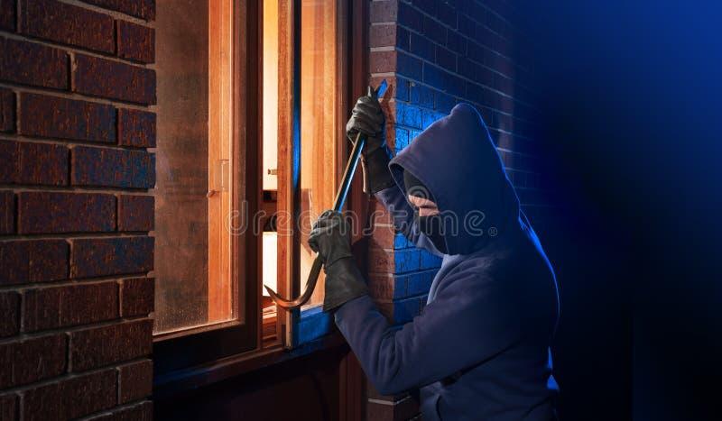 Inbreker die in een huis breekt royalty-vrije stock foto