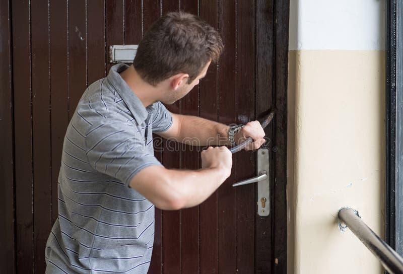 Inbreker die in een huis met een koevoet proberen te breken stock foto's