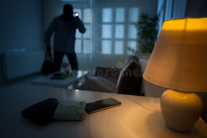 Inbreker in een gewoond in huis stock afbeelding
