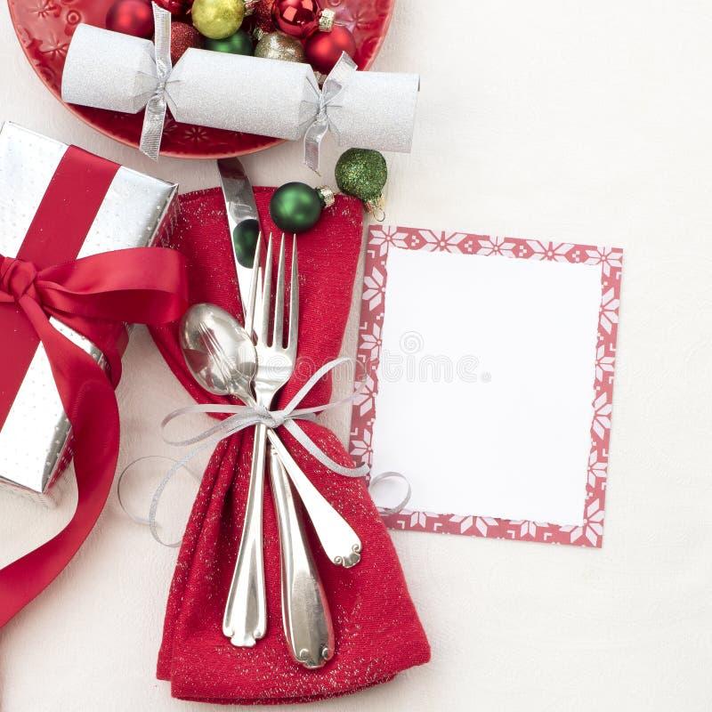 Inbrott för jultabellställe som är rött som är vitt och silver med bestick, en gåva och partismällare på vit torkdukebakgrund med arkivbild