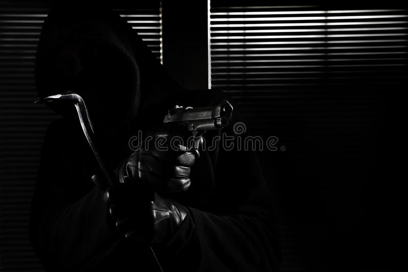 Inbrott och röveri skicklig yrkesmässig maskerad inbrottstjuv som rymmer ett vapen och en kofot och bryter in i huset, handslut u royaltyfri fotografi