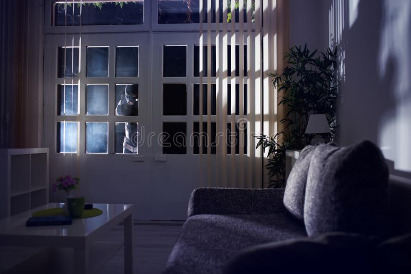 Inbrott som bryter in i ett hem på natten royaltyfri bild