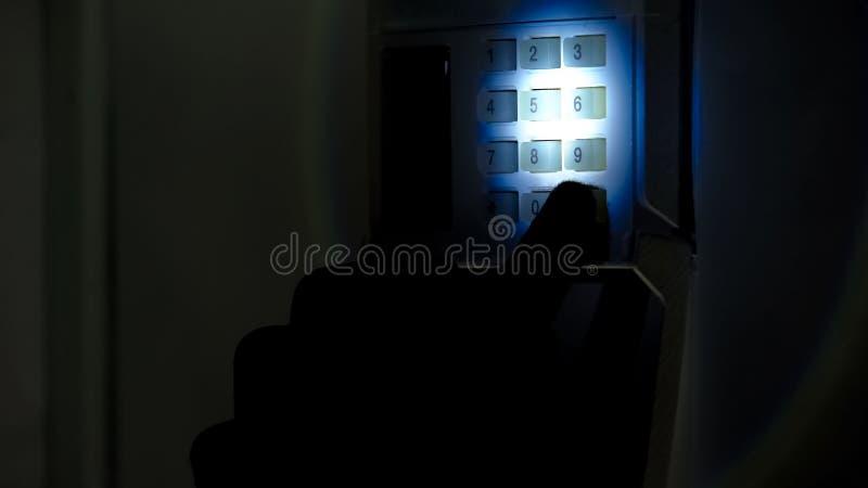 Inbrottstjuv med ficklampan som försöker att avväpna säkerhetslarmsystemet, housebreaking royaltyfria bilder