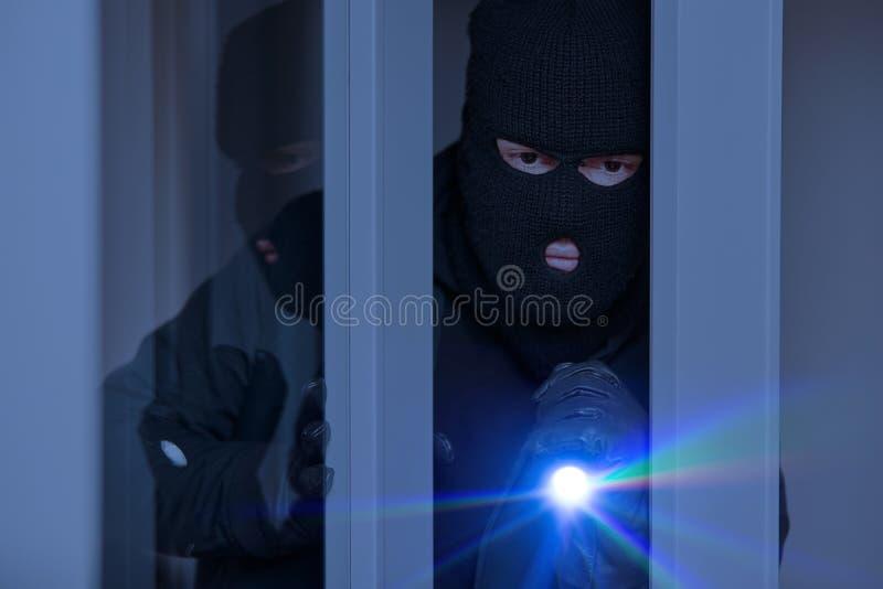 Inbrottstjuv på natten på fönstret av huset royaltyfri bild