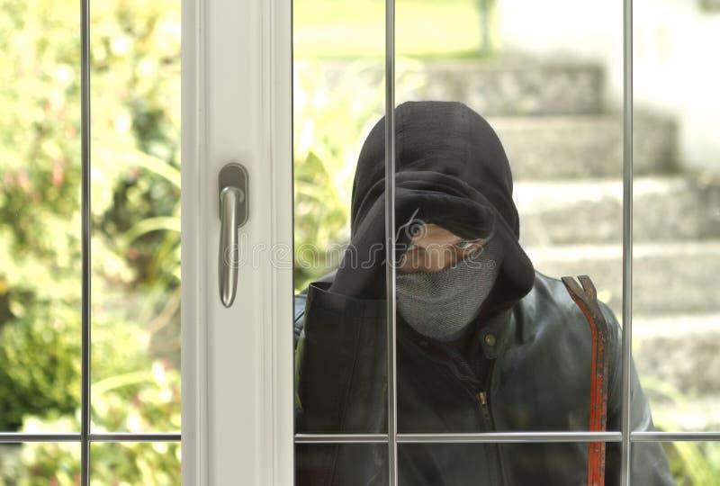 Inbrottstjuv som bryter i ett hus royaltyfri illustrationer