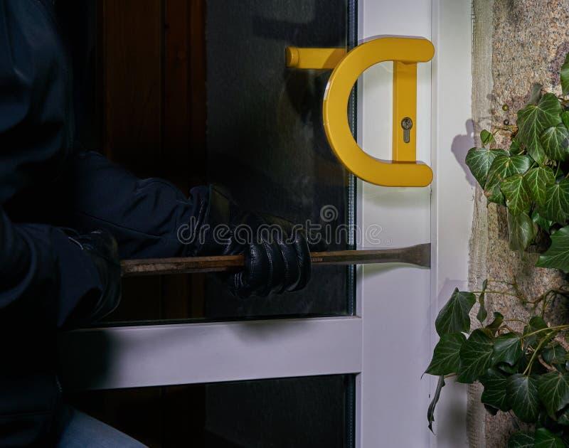 Inbrottstjuv som försöker att få in i ett hus genom att använda en kofot arkivbilder