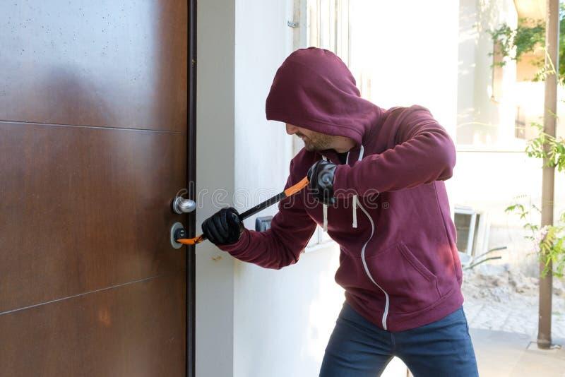 Inbrottstjuv som försöker att tvinga ett dörrlås royaltyfri fotografi