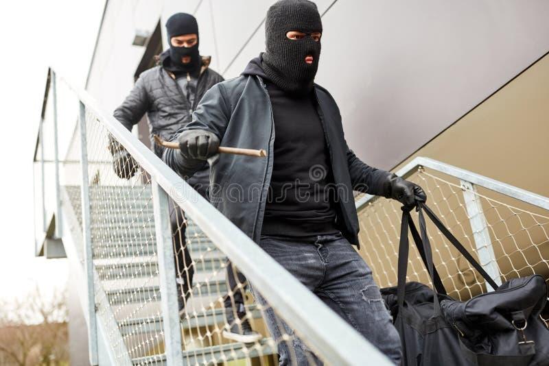 Inbrottstjuvar flyr med byte över trappa arkivbilder
