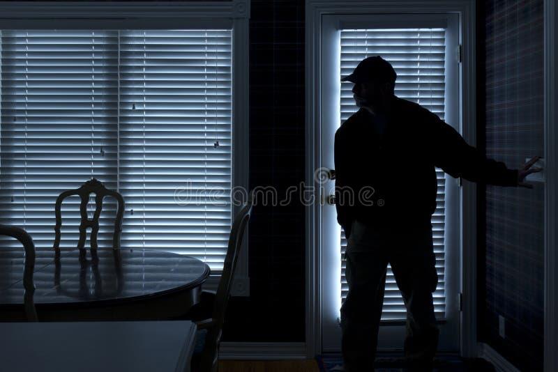 InbrottstjuvBreaking In To hem på natten till och med baksida  royaltyfria bilder