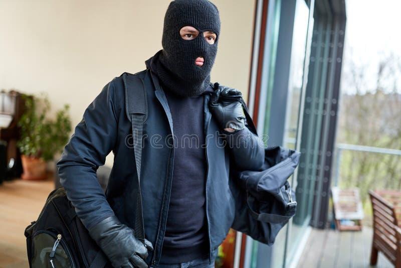Inbrottstjuven flyr från hus med rovet royaltyfri bild